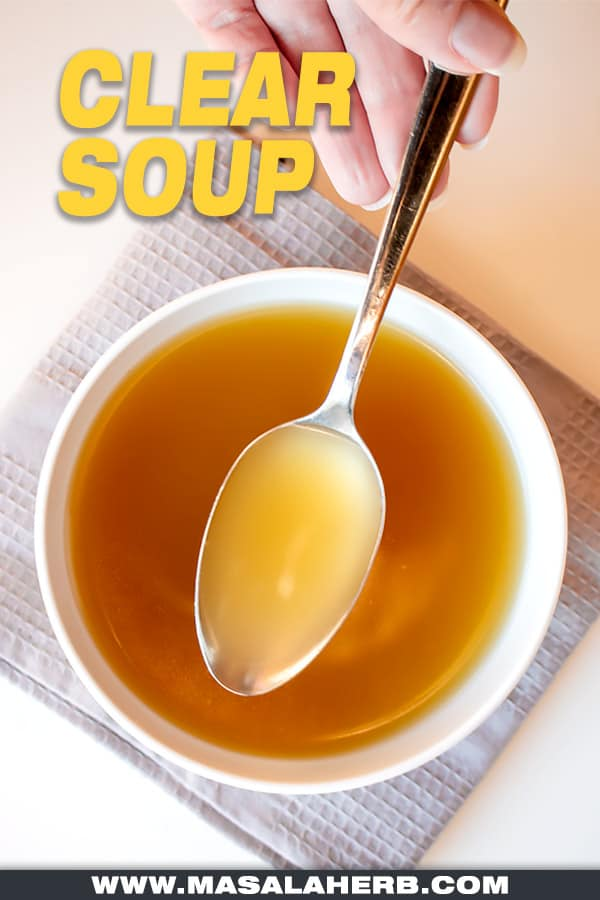 clear soup in a bowl and spoon