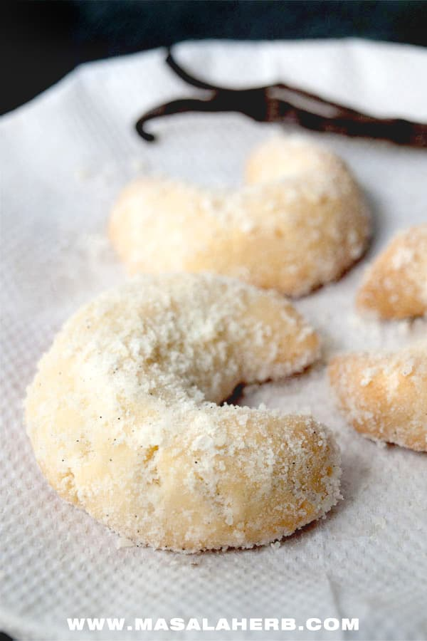 Vanillekipferl - Austrian Vanilla Crescent Cookies Recipe [Egg-less] Our family recipe with homemade vanilla sugar coated vanilla crescent cookies. you can use almond flour or walnut flour or hazelnut flour to make these melt in the mouth cookies! www.Masalaherb.com #recipe #masalaherb #cookies #christmas #austrian
