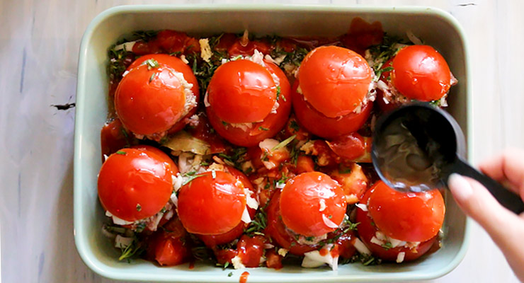 add tomato sauce and seasoning to the baking dish with stuffed tomatoes