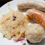 Sauerkraut bread dumpling and sausages on a plate