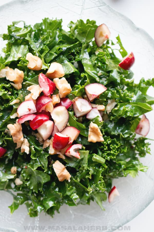 kale salad topped with fresh cranberries and walnuts