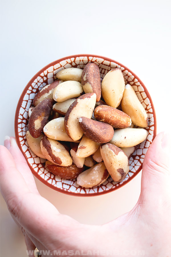 hand holding bowl with brazil nut