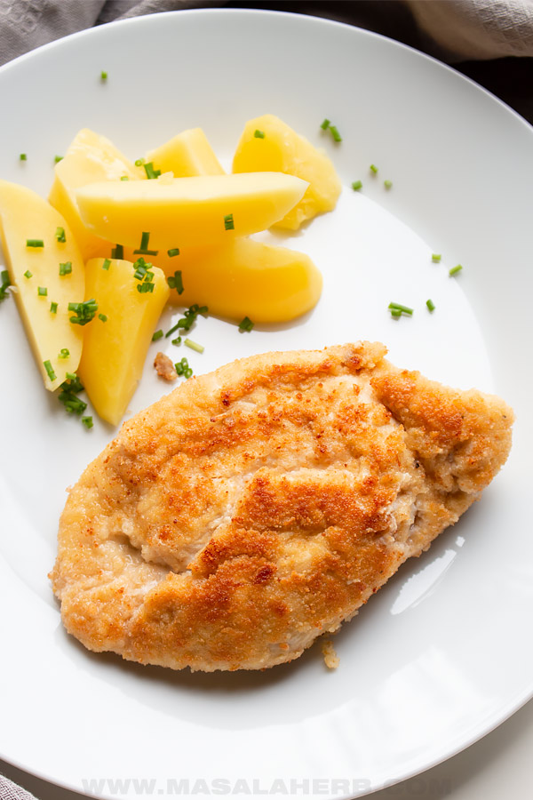 chicken cordon bleu breaded serve with parsley potato wedges