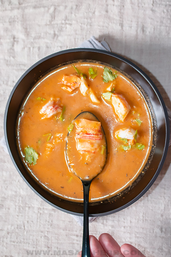 top down view of lobster bisque in a bowl and spoon