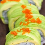 bright green dragon roll close up with tobico orange fish roe as topping