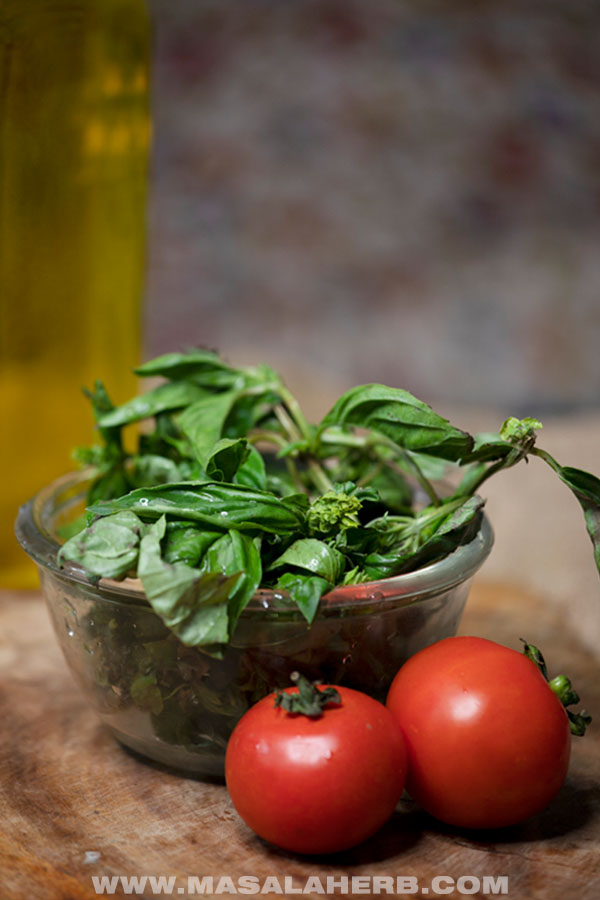 fresh tomatoes and basil in a bowl with olive oil in a bottle in the background