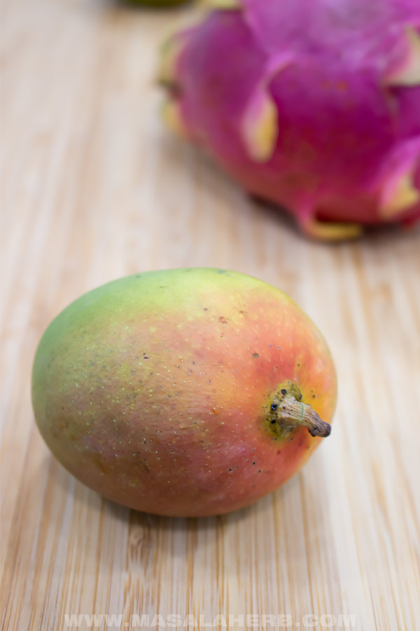 mango whole with dragon fruit in the back