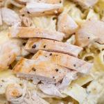 cut chicken breats over alfredo pasta